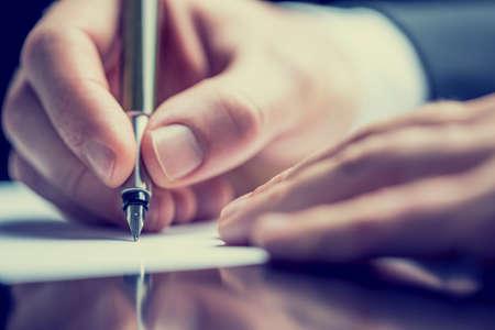 Retro effetto sbiadito e tonica immagine di un uomo che scrive una nota con una penna stilografica.