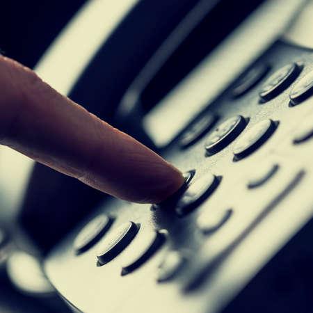 Retro Bild eines Finger Drücken einer Zifferntaste auf dem Telefon, um einen Anruf zu tätigen.