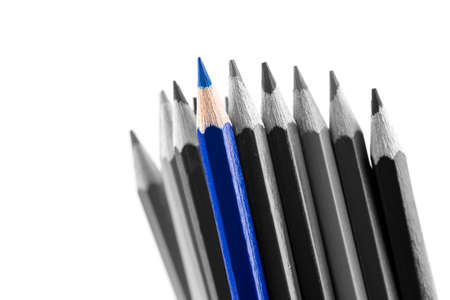 Pile of sharp colored pencils, with different hues, from black to light grey and a blue outstanding one, close-up on white . photo