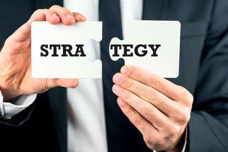 Nahaufnahme der Hände eines Geschäftsmannes, zwei Teile eines Puzzles mit dem Wort Strategie aufteilen und davon konzeptionelle von uns denken, Planung und Problemlösung. Standard-Bild - 26535918