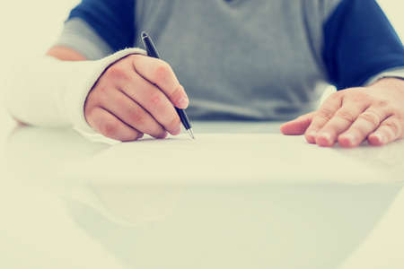 broken contract: Man with his arm in a plaster cast from a fractured wrist or arm writing a letter or signing a document using his injured hand on a white table with copyspace. With retro filter effect.