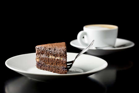 chocolate slice: Slice of delicious fresh chocolate cake served with a cup of aromatic cappuccino coffee on a dark with copyspace.