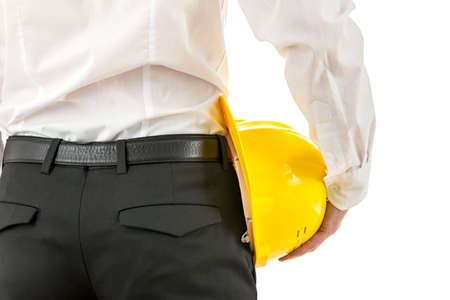 Engineer or architect holding a yellow hardhat under his arm, close up view from behind of the stylish pants and white shirt with the mans hand.