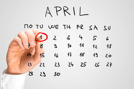 Hand getrokken kalender voor april op een virtuele interface of scherm met de eerste geringd in het rood door een man die een pen marker, close-up van zijn hand. Dwazen dag concept.