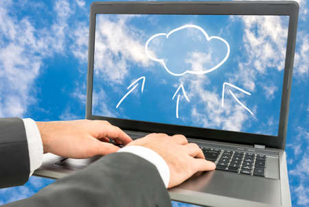 data synchronization: Businessman using cloud computing sitting typing on his laptop keyboard with an image of blue sky and clouds on the screen continued as the background for the image. Stock Photo