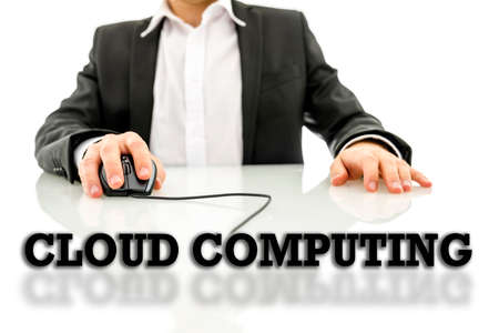 Cloud computing text on a reflective surface with a businessman using a wired computer mouse in the background conceptual of an online database and global connectivity.