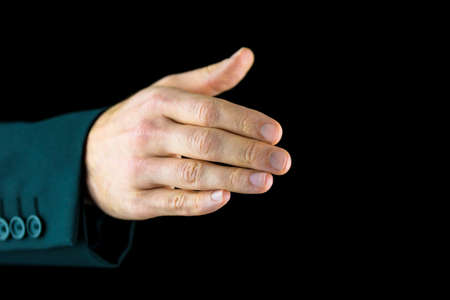 Close-up of the right hand of a man, wearing black business suit, ready for a handshake, symbol of agreement or partnership, on black background. photo