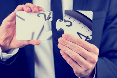 가까운 그의 손을 위로, 마감, 시간 관리 및 문제 해결의 개념 시계의 다이얼 부분을 묘사 한 퍼즐 조각을 들고 사업가입니다.