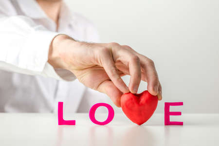 Conceptual image of Love with a man holding a red heart replacing the letter V in the word Love in red text standing on a reflective white table to celebrate Valentines, a wedding or anniversary. photo
