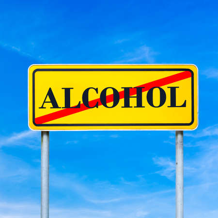 Alcohol abuse on a yellow traffic sign crossed through in red against a sunny blue summer sky, conceptual image.  photo