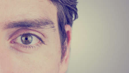 eye close up: Close up of the eye and ear of a man looking straight ahead showing eyebrow