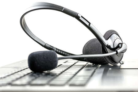 ヘッドセットは、テレマーケティング、コール センター、クライアント サービスやオンライン サポートの概念のラップトップ コンピューターのキ