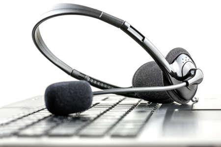 klawiatura: Słuchawki leżącego na klawiaturze komputera przenośnego koncepcyjnego telemarketingu, call center, obsługi klienta lub pomocy online. Zdjęcie Seryjne