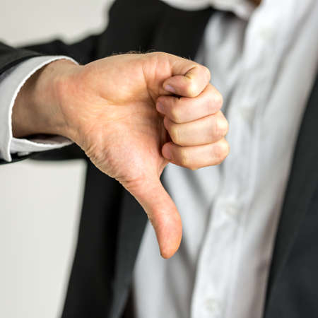 dissatisfaction: Man giving a thumbs down gesture of disapproval showing his negativity and dissatisfaction, close up of his hand. Stock Photo