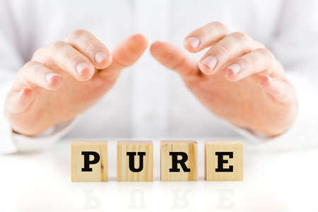 pureness: Conceptual image of a man in shirtsleeves holding his hands protectively above a line of wooden cubes with the word Pure.