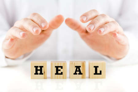 sheltering: Conceptual image with the word Heal on wooden blocks or cubes protected by the hands of a man sheltering them from above. Stock Photo