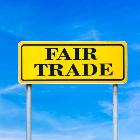 developing: Yellow traffic sign with the text Fair trade against a clear blue summer sky.
