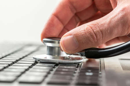 laptop repair: Conceptual image of the hand of a man checking the health of his laptop computer using a stethoscope as he checks for malware and viruses or any electronic malfunctions. Stock Photo
