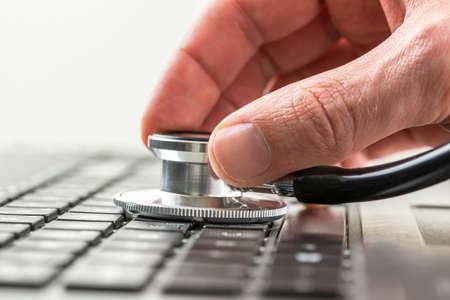 Conceptueel beeld van de hand van een man het controleren van de gezondheid van zijn laptop computer met een stethoscoop als hij controleert op malware en virussen of elektronische storingen. Stockfoto