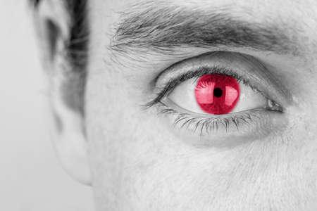 Zwart-wit beeld met selectieve kleur van een jonge man met rode ogen, close-up van zijn oog en wenkbrauw.