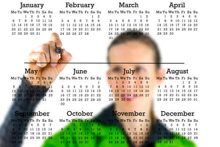 Virtual calendar on a transparent interface with a woman writing from behind with a marker pen in copyspace between the months. photo
