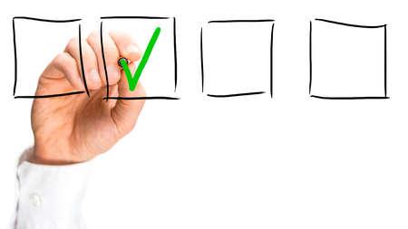 Man tikkende een hand getrokken selectievakje in een lijn van vier lege dozen op een virtuele interface met een groen vinkje conceptuele van succes, ja of aanvaard, alleen met de hand op wit met copyspace. Stockfoto