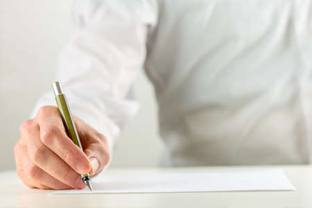Close up of the hand of a man writing with a fountain pen on a sheet of blank white paper or document in a conceptual image.