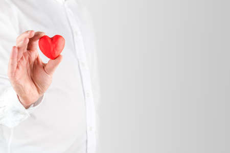Women's health: Close up of the had of a man in a white shirt holding a small red Valentines heart between his fingers showing his love for a sweetheart or loved one, with copyspace.