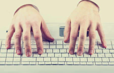 inputting: Toned effect image of a man typing on a computer keyboard inputting data or information. Stock Photo
