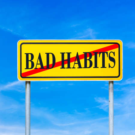 Bad Habits prohibited - conceptual image with the words Bad Habits crossed through in red on a yellow traffic sign against a sunny clear blue sky. photo