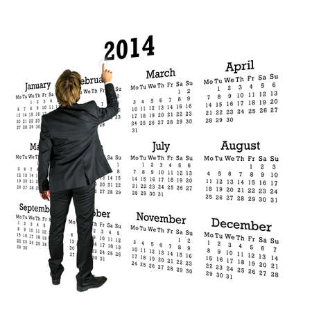 Businessman in a suit standing with his back to the camera in front of a 2014 calendar on a white background pointing to the year with his finger. photo