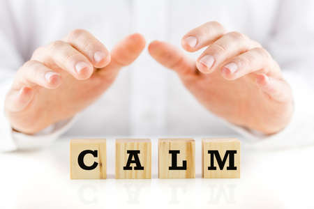 shirtsleeves: Man in shirtsleeves holding his hands protectively above wooden cubes with the word Calm.