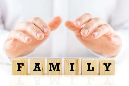 guarding: Man holding protective hands above the word - Family - on a line of wooden cubes as he safeguards and protects them.