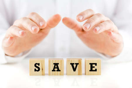 necessary: Conceptual image of a man shielding the word Save written on a row of wooden cubes with his hands.