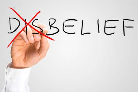 desconfianza: Incredulidad - Creencia, un concepto de los opuestos con un hombre que cruza a trav�s de la Dis de la palabra escrita a mano Incredulidad en una pantalla virtual con copyspace.