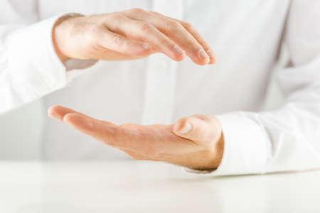 上記保護ジェスチャーで彼の手をカッピング男し、製品の配置または概念的オブジェクト用の空の領域の下のクローズ アップ表示白いシャツに対し