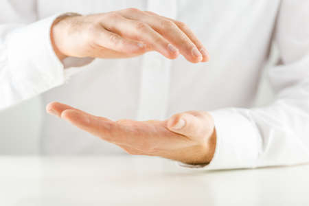 healing chi spiritual: Man cupping his hands in a protective gesture above and below an empty space for your product placement or conceptual object, close up view of the hands against a white shirt.