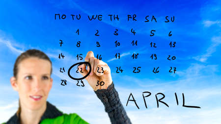Woman marking Earth Day on a hand drawn calendar for the month of April on a virtual interface ringing the date of the 22nd raising awareness of conservation and the ecology. photo