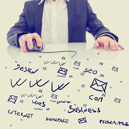 glass topped: Businessman using a computer mouse sitting at a glass topped desk covered in hand-drawn computing, business and e-commerce icons and notations in a conceptual image. With retro filter effect. Stock Photo