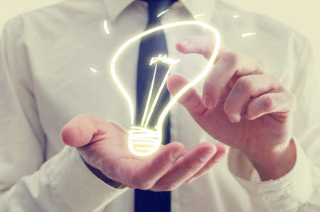 ingenious: Retro image of businessman holding a creative light bulb icon in his hands conceptual of ideas, inspiration, imagination, and innovation.