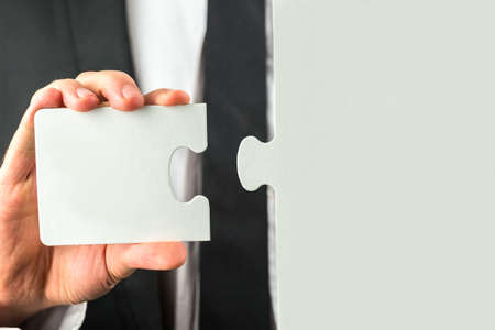 complement: Businessman holding the missing piece to complete the puzzle in his hand conceptual of the solution to a problem or completing a task.