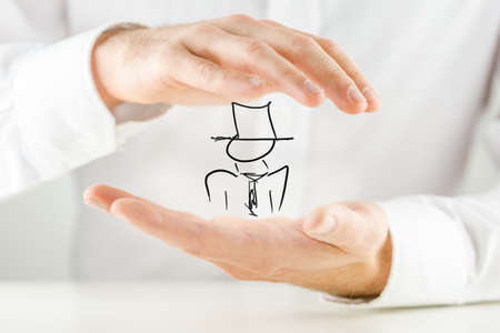 mentalist: Man holding a hand-drawn figure of a businessman or performing artist wearing a hat in his hands in a conceptual image, close up of the hands.