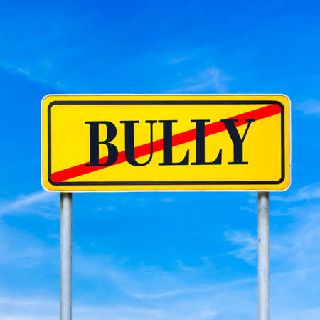 spiteful: Yellow street sign with word Bully crossed through against clear blue sky.