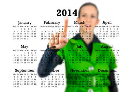 Woman standing behind a 2014 calendar on a transparent virtual interface or screen activating a button under the year with her finger. photo