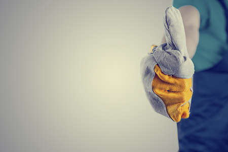 tradesmen: Closeup of handyman hand in a protective glove making thumbs up sign.