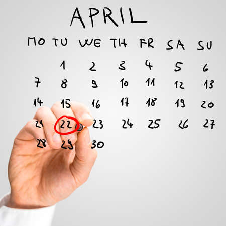 encircling: Male hand encircling the date of April 22 on a monthly calendar placed on a virtual screen, in order to remember to celebrate International Mother Earth Day.