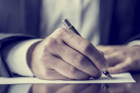 authors: Man signing a document or writing correspondence with a close up view of his hand with the pen and sheet of notepaper on a desk top. With retro filter effect.