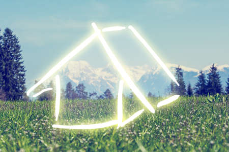 Hand-drawn house in white on a green field against a backdrop of a scenic mountain landscape, conceptual of a dream eco house and ownership. photo