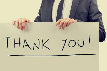 you black: Efecto retro desvanecido y la imagen de un hombre de negocios tonos celebraci�n de una cartelera con Gracias! firmar en �l.