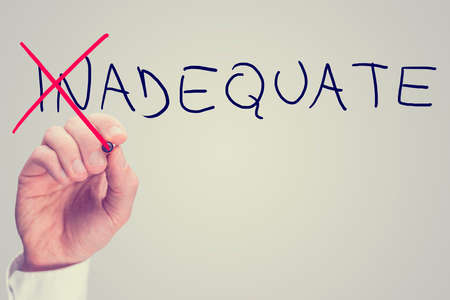 lacking: Concept of Inadequate versus Adequate with a business man crossing through the In in the word Inadequate with a red pen on a virtual screen with blank white copyspace, retro toning effect.